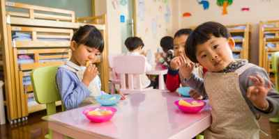 Three toddler eating on a white table
